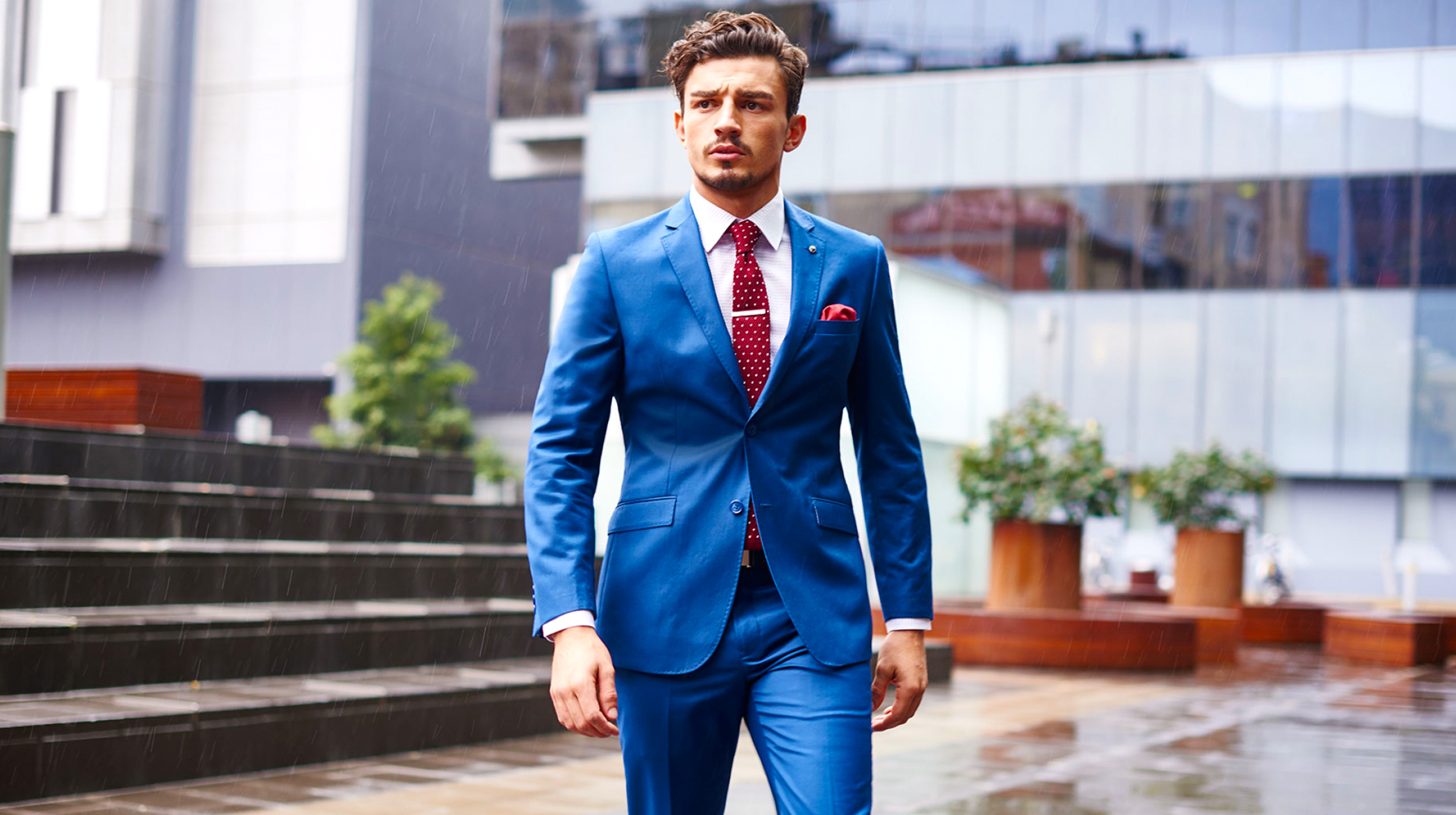 Blue suit matched with a white shirt and a red tie