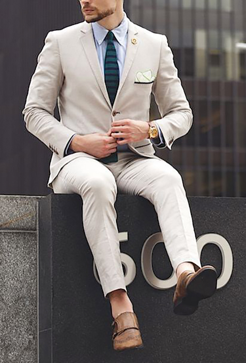 beige suit matched with a pale blue shirt, brown shoes, and dark green tie