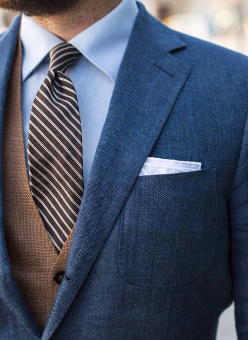 Brown vest with blue jacket, pale blue shirt and brown tie