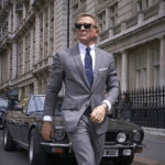 James Bond (Daniel Craig) in a light-grey suit and black wayfarers