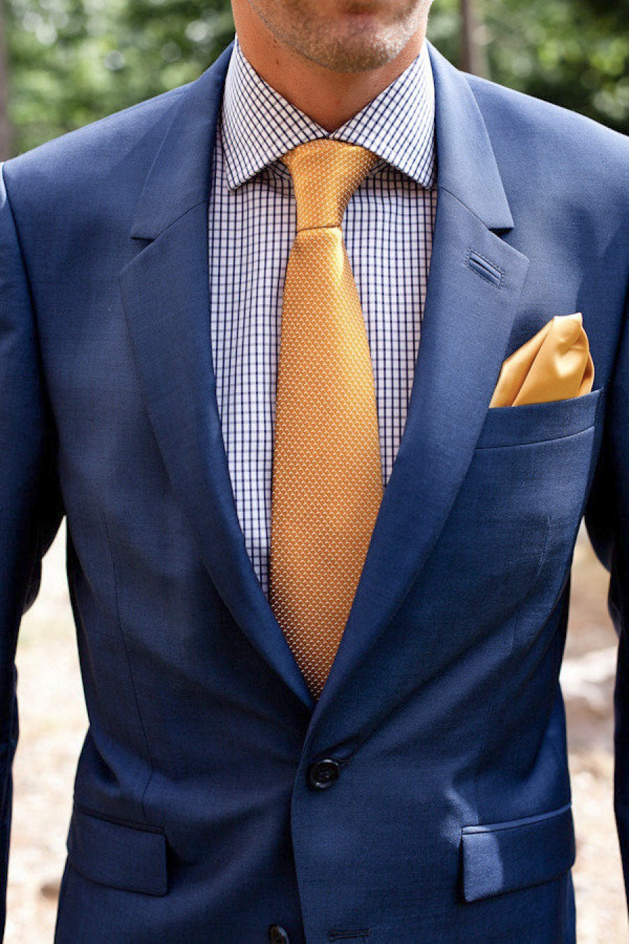 navy suit and checkered shirt with orange pocket square