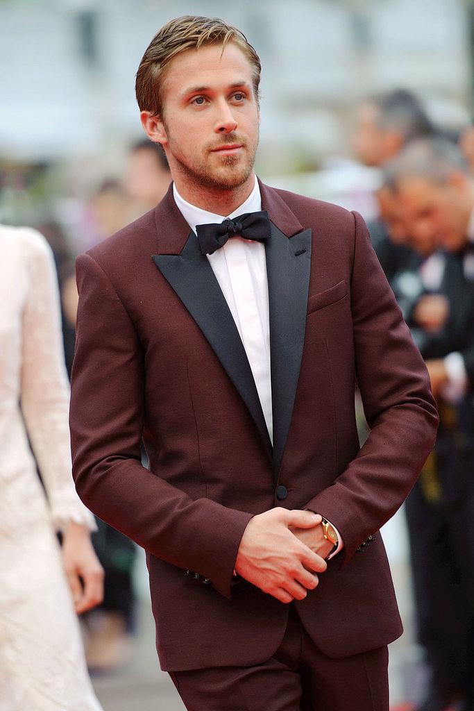 Ryan Golsing wears burgundy peak lapel tuxedo with black bow tie at a black-tie event