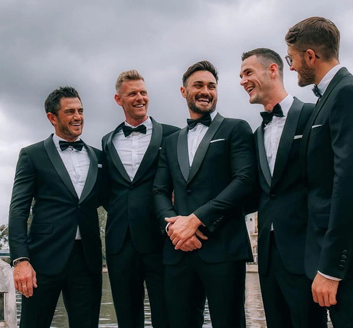 wearing green suits and tuxedos to a wedding